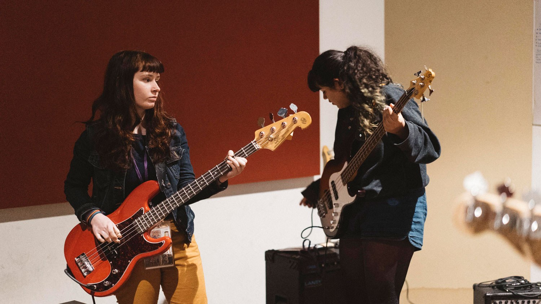 Two girls playing guitar