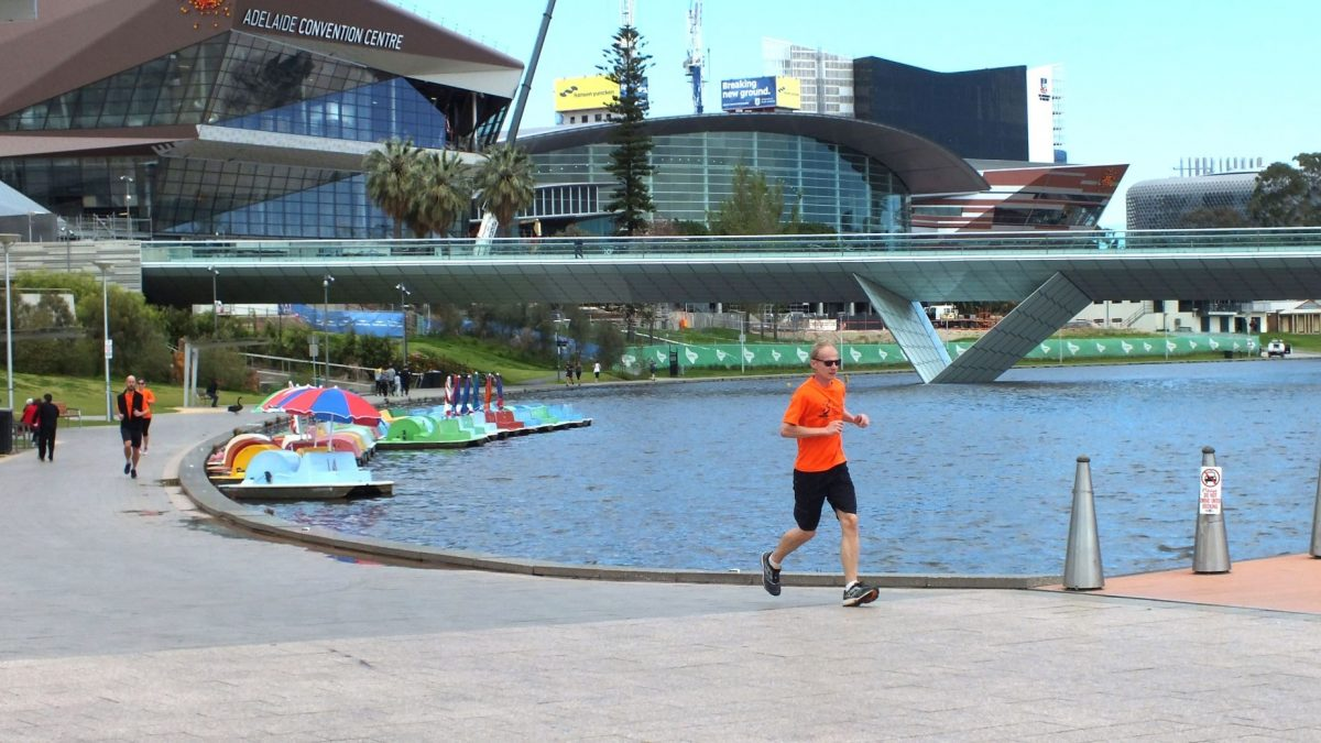 People running along river torrens corporate cup