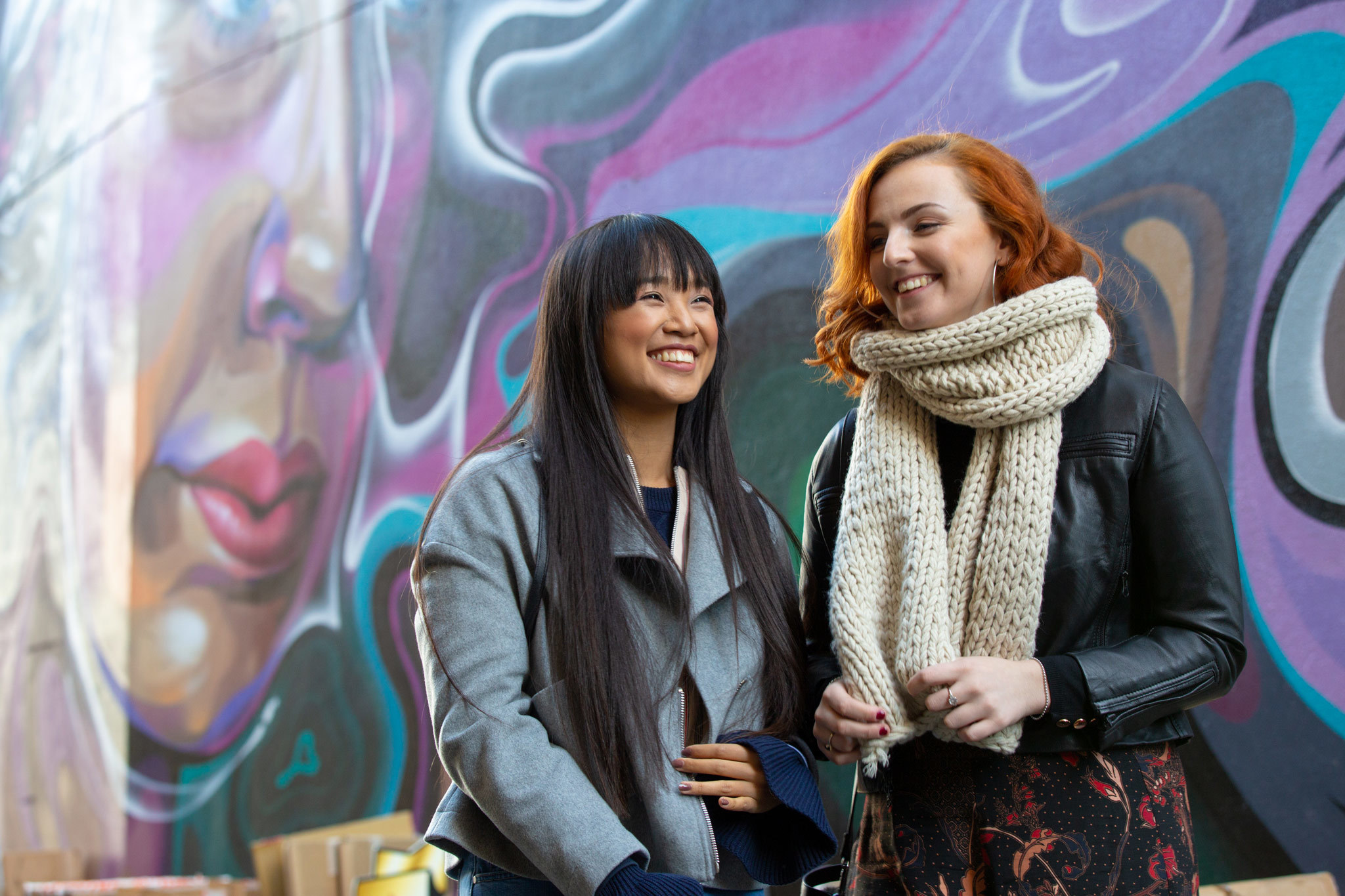 Women laughing in front of a street art mural in Adelaide